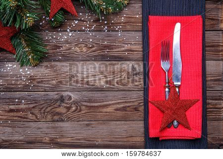 Christmas table place setting with fork and knife, decorated red star and red napkin, and christmas pine branches with toys. Christmas holidays background.
