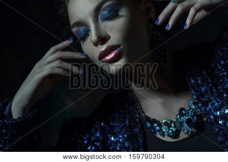 Glamour fashion woman portrait. Dark tones.