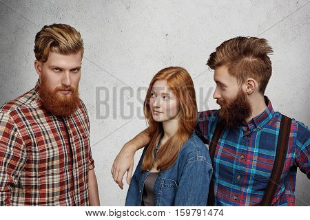 Love Triangle Between Two Men And Woman. Bearded Hipster Looking At Camera With Furious Expression,