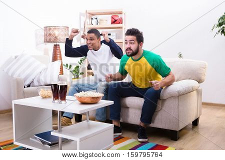 Image of friends men watching football game, screaming and shouting, drinking alcohol drinks and eating pop corn at home.