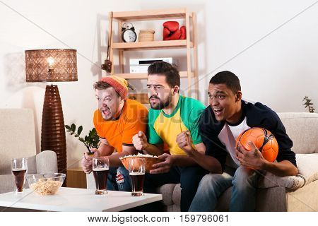 Picture of friends watching football game on TV while spending their weekends at home with alcohol drinks and pop corn. Football concept.