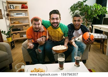 Image of happy friends watching football game. Handsome men looking at TV screen and waiting for special, emotional and exciting moments in game.