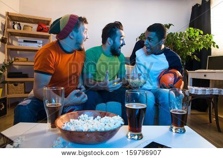 Group of friends sitting on sofa or couch and watching football game on TV. Happy friends looking excited and amazed. Football concept.
