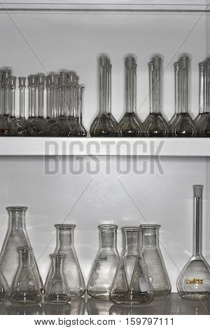 Scientific flasks displayed in shelves at laboratory