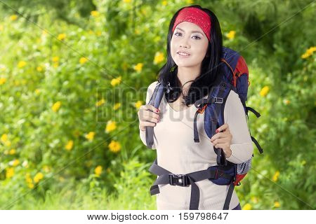 Portrait of a beautiful traveler smiling at the camera while carrying rucksack in the forest