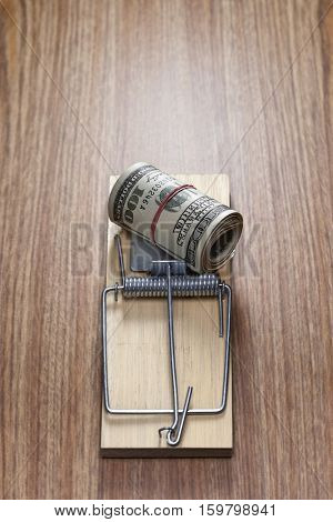 Roll of dollar bills in mouse trap