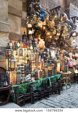 Huge group of stacked illuminated copper lanterns over background of old decorated stone wall and basalt tiles floor at Khan El Khalili bazaar district one of Old Cairo's main attractions for tourists and Egyptians alike