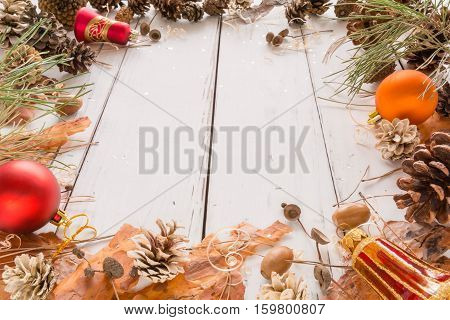 Abstract Christmas Frame With Cones, Pine Bark, Acorns, And Toys. White Wooden Background.