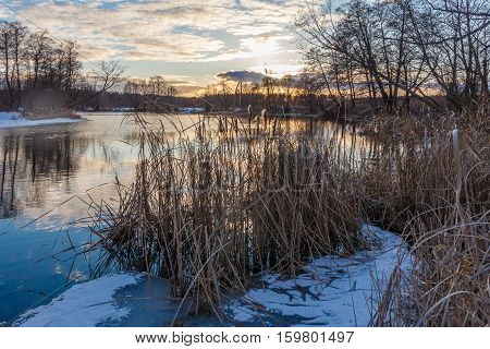 Sunset in March over a big river, the reeds along the banks, the remnants of ice