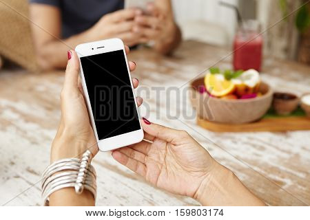 White Smart Phone With Blank Copy Space Screen In Woman's Hands Over Cafe Table. Cropped Shot Of Fem