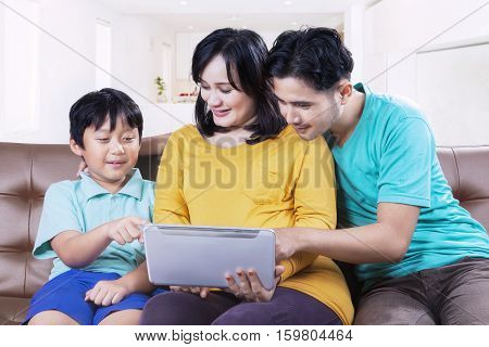 Parents and boy pointing digital tablet while sitting on the sofa