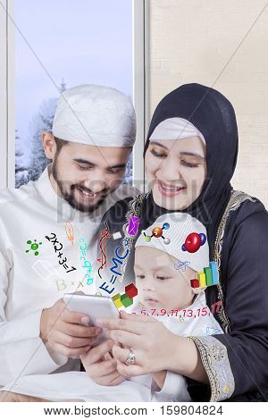 Portrait of smiling arabian parents teach math on smartphone with winter background on the window