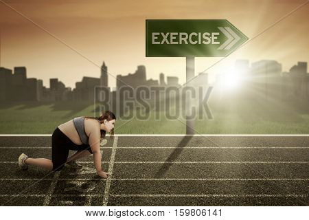 Picture of young woman ready for running with exercise word at the signpost