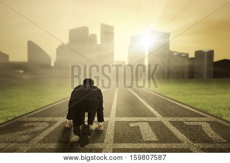 Businessman wearing a formal suit in ready position to run toward the city with numbers 2017 on the road