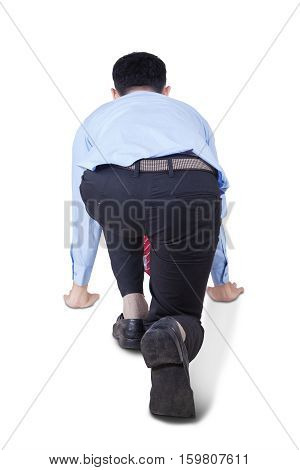 Back view of a young businessman in ready position to run isolated on white background