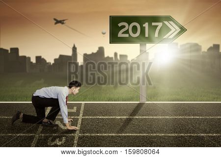Portrait of a middle eastern entrepreneur in ready position on the track with numbers 2017 on the road sign