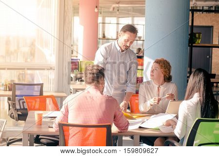 Business people working in board room all together in office. Boss saying something to his worker lady and explaining his position about company and partners.