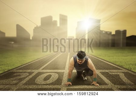 Image of an overweight male ready to run and try to lose weight with numbers 2017 on the asphalt track