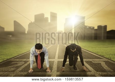 Image of two businessmen in ready to compete and try to chase their dream with numbers 2017 on the running track