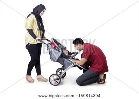 Picture of young parents playing and strolling with their baby on the stroller isolated on white background