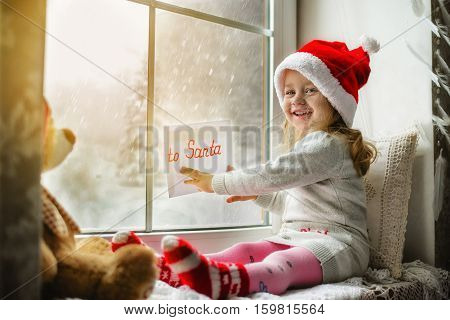 Merry Christmas and happy holidays Cute little girl sitting by the window with a letter to Santa Claus and looking at the winter forest. Room decorated on Christmas. Kid enjoys the snowfall.