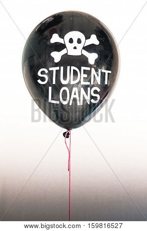 The words student loans and a skull and cross bones on a balloon illustrating the concept of a student loan debt bubble and its danger to the US national debt and risk for the next GFC.