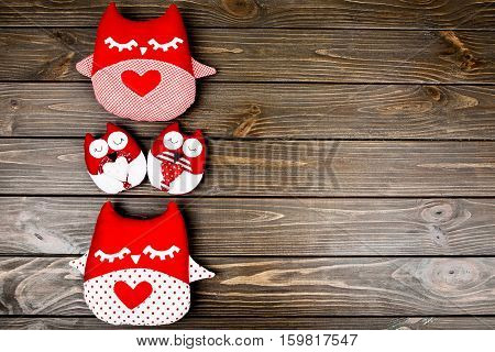 Two Big And Two Small Soft Red Owls Lying On Wooden Surface