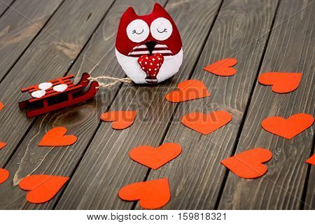 Red Soft Owl With Sledge Lying On Wooden Surface