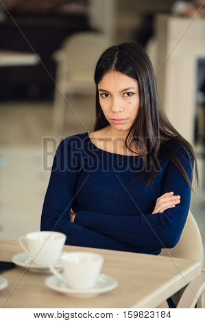 Angry young woman with crossed arms at cafe.