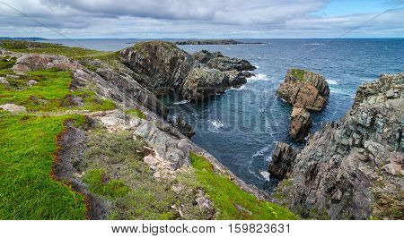 Huge rock & boulder outcrops along Cape Bonavista coastline in Newfoundland, Canada.   Coastal layered slabs of stone and rock that show their layers of formation over millions of years.