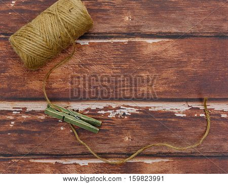 Rough thread reel with wooden pin lying on rough wood background. Copy space.