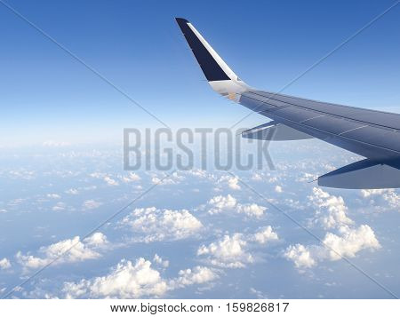 Wing of airplane fly over the blue sky and white cloud