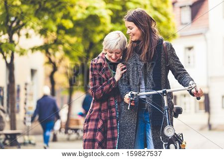 Two young women walking in Berlin. Blonde and brunette women one is holding a bicycle the other woman is embracing and leaning on her shoulder. Friendship and lifestyle concepts.