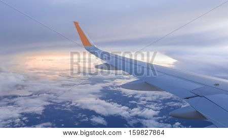 Wing of airplane fly over the blue sky and white cloud in sunset time