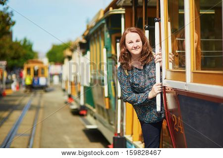 Tourist Taking A Ride In Famous Cable Car In San Francisco