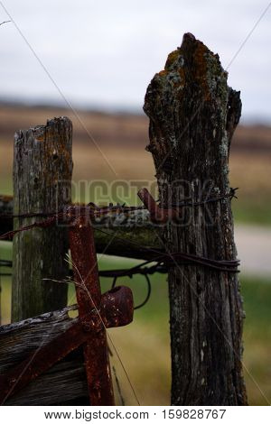 Old barn fence post with rusty metal support, reinforcements and barbed wire in rural setting