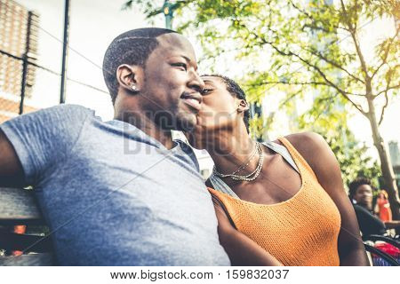 Couple in love at first date sitting on a bench and cuddling