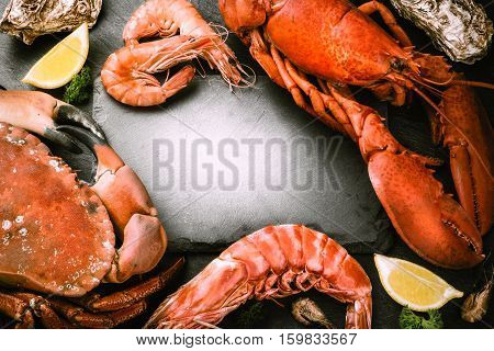Food frame with crustacean for dinner. Lobster crab jumbo shrimps and oysters on dark background with copyspace