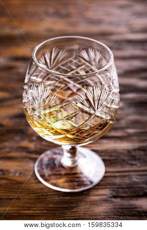 crystal glass with cognac on a wooden background evening relaxation