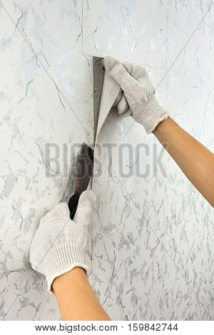hand scraping off old wallpaper with spatula
