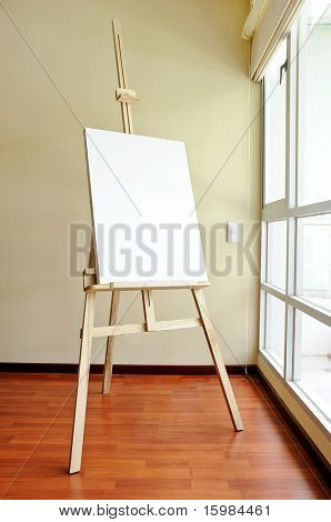 Blank canvas on a wooden tripod in the studio