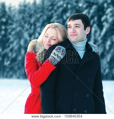 Portrait Happy Loving Young Couple Hugging In Winter Day Over Snowy Trees Forest Background
