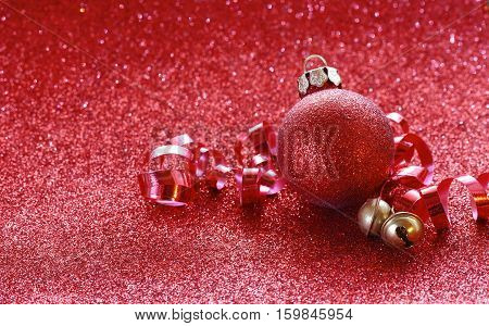 Red christmas glitter background ball jingle bells on ribbon selective focus