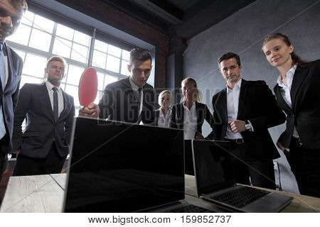 Business people play ping pong on office table with laptops
