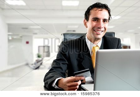 e-commerce concept: business man paying online with his credit card at office