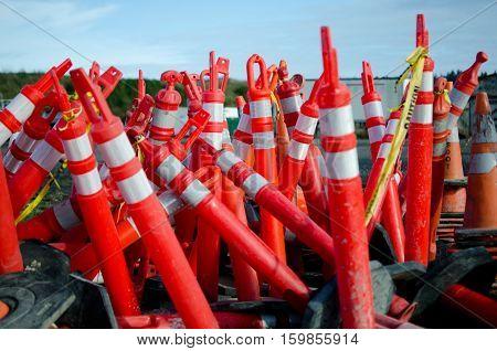 Rest place of dozen of white and orange construction fence poles.