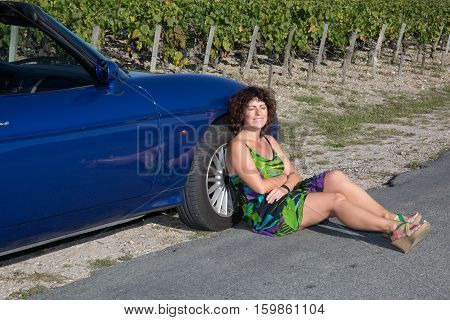 Happy lovely girl near his convertible car