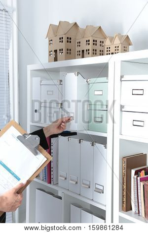 File folders, standing on shelves in the background.
