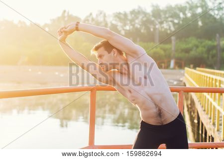 Young athlete man doing side bend exercise