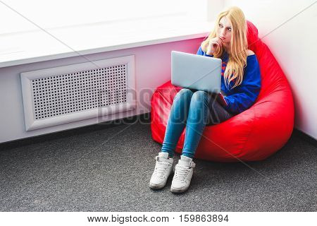 blonde with a laptop lost in thought sitting on a chair-sac